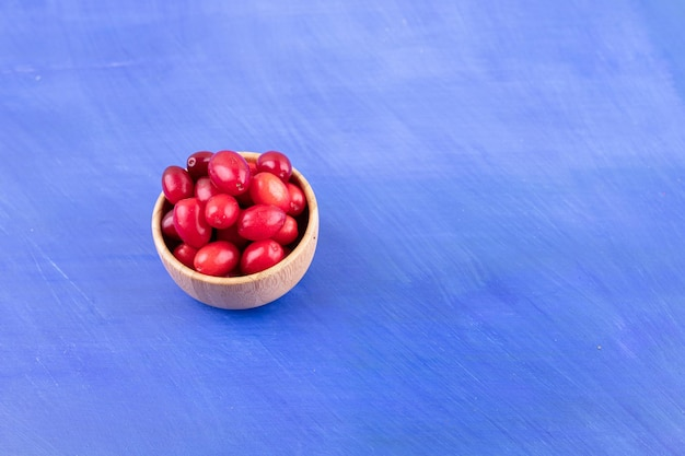 A small wooden bowl full of rosehips on blue surface