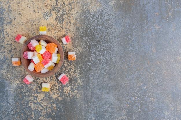 Una piccola ciotola di legno piena di marmellata zuccherina. foto di alta qualità