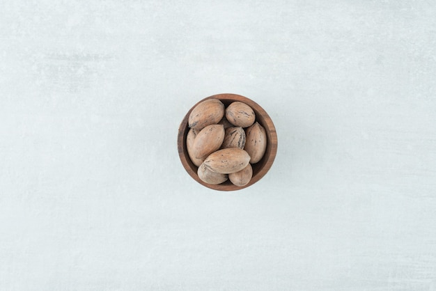 A small wooden bowl of nuts on white background. high quality photo