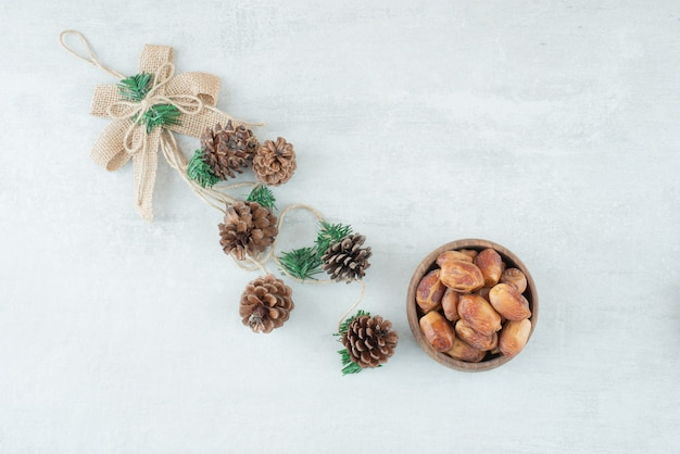 A small wooden bowl of nuts with pinecones on white background. high quality photo