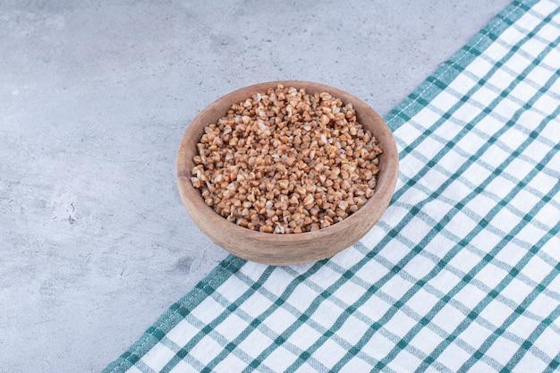 대리석 표면에 펼쳐진 수건에 메밀의 작은 나무 그릇