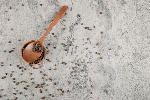 Small wooden bowl of pepper grains on marble background