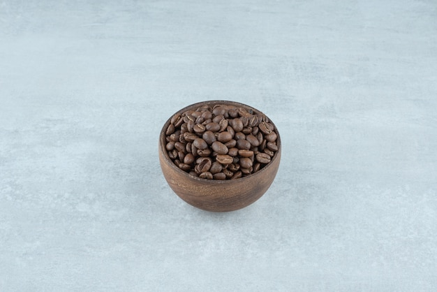 A small wooden bowl with coffee beans on white background. high quality photo