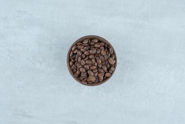 Una piccola ciotola di legno con chicchi di caffè su bianco