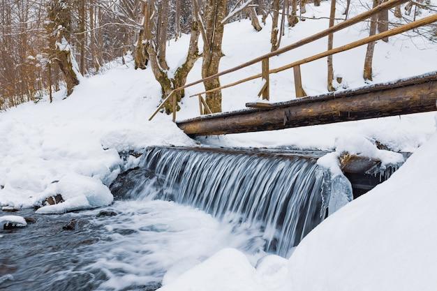 겨울에 차가운 산 스트림 위에 작은 나무 다리