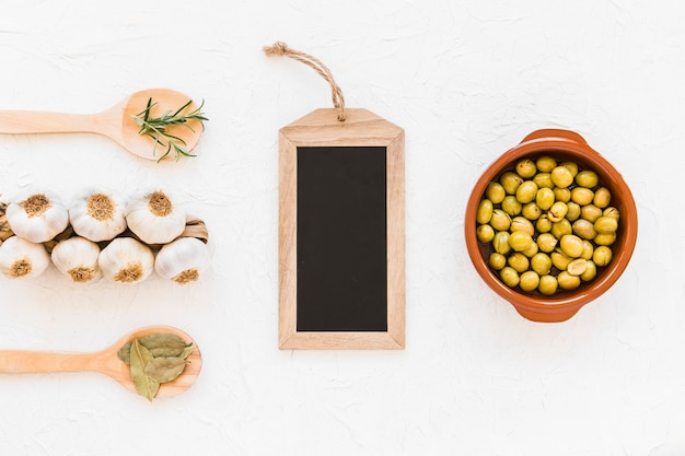 Small wooden chalk board with bunch of garlic bulbs, olives and herbs