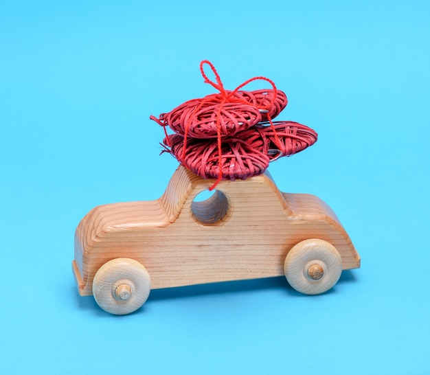Small wooden children's car carries a wicker red heart