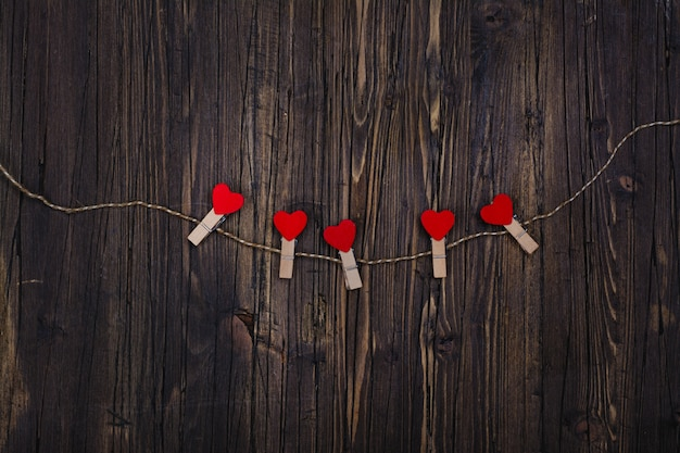 Small wooden clothespin with red hearts hanging on rope
