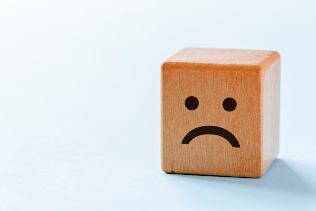 Small wooden dice with sad emotion