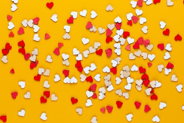 Маленькие деревянные сердечки на желтом фоне. креативная идея. поздравительная открытка ко дню святого валентина.