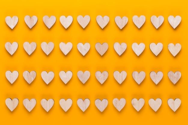 Маленькие деревянные сердечки на желтом фоне. креативная идея. валентинка.