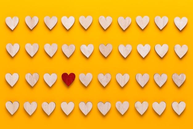 黄色の背景に小さな木の心。創造的なアイデア。バレンタインデーのグリーティングカード。