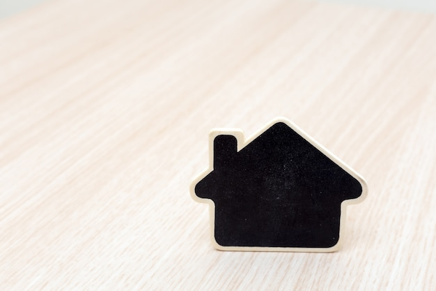 テーブルの上に小さな木の家。不動産事業のコンセプト。