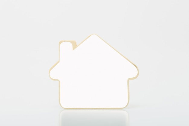 Small wooden home with white blank on tabel. concept for real estate busines.