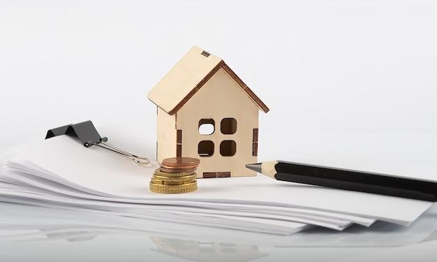 Небольшой деревянный дом и монеты и лист бумаги, бизнес
