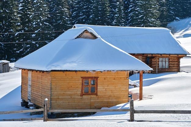 겨울 산의 키 큰 소나무로 둘러싸인 신선한 눈으로 덮인 작은 목조 주택.