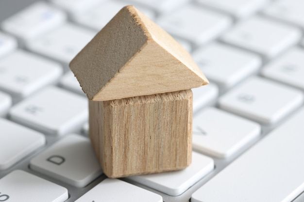 Small wooden house made of cubes stands on computer keyboard search for rent and purchase of