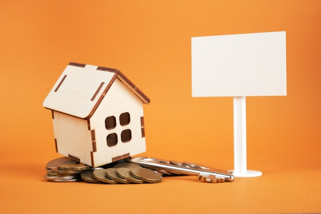 Small wooden house model, white blank sign and a pile of coins on a brown background