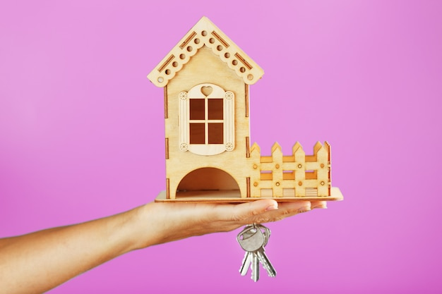 A small wooden house with keys in hand on a pink background.