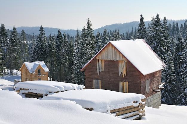 Небольшие деревянные домики в красивом заснеженном горном лесу. лесной дом в снегу