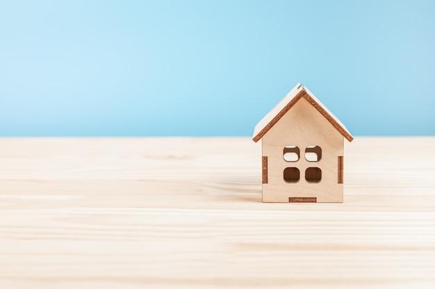 나무 테이블에 작은 나무 모델 하우스. 파란색 배경에 미니 주거 공예 집입니다. 작은 집 모델