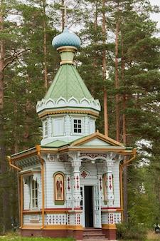 Маленькая деревянная православная церковь на фоне лесных деревьев. деревянная церковь в лесу