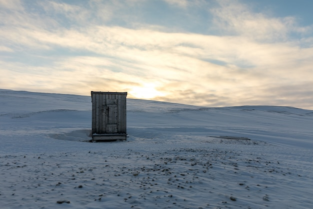 Small wooden outhouse hut in the middle of arctic landscape in winter