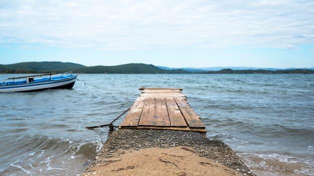 Ormospanagiasのエーゲ海沿岸近くのボート付きの小さな木製の桟橋
