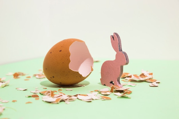 Small wooden rabbit with broken egg on table