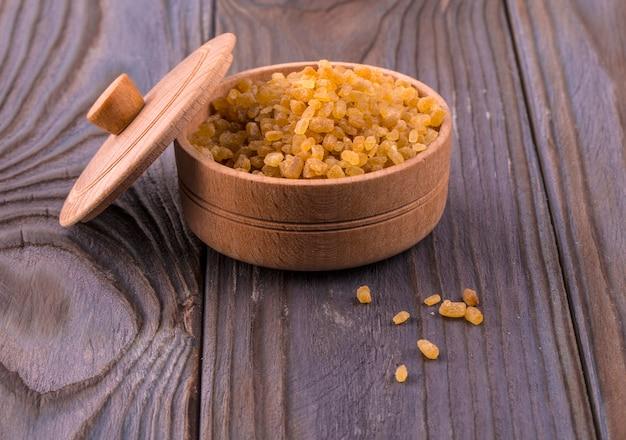 Небольшая деревянная круглая миска, полная коричневого тростникового сахара на деревянных фоне.