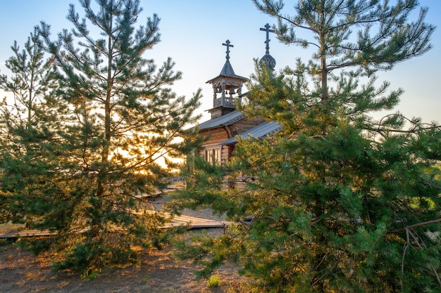 Small wooden russian orthodox church between tall trees in the forest with beautiful sunlight