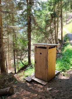 Small wooden toilet in the woods of the alps in austria