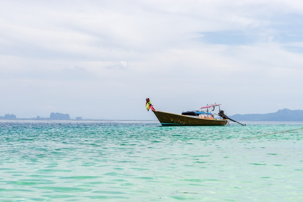 Small wooden tourist boat anchoring on the beach with view of white cloudy sky