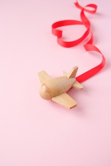 Small wooden toy airplane carries red ribbon in the shape of heart