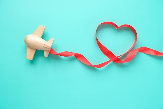 A small wooden toy airplane carries valentine's elements. vapor trail of sequins in the shape of heart, and red ribbon in the shape of heart. valentine's day