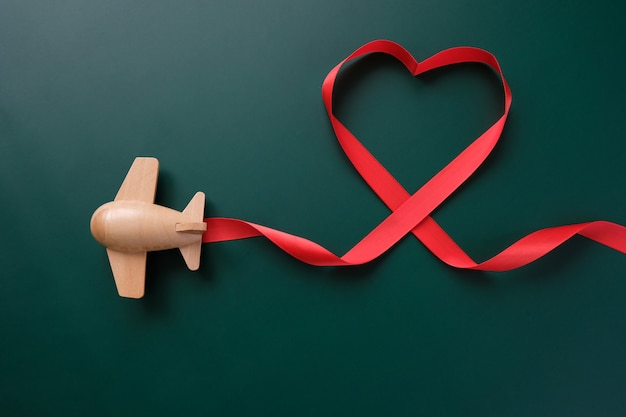 A small wooden toy airplane carries valentine's elements. vapor trail in the shape of heart, and red ribbon in the shape of heart. valentine's day
