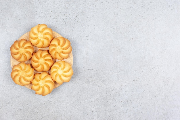 A small wooden tray of cookies on marble background.