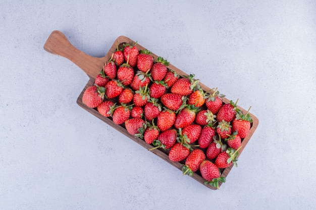大理石の背景に新鮮なイチゴで満たされた小さな木製トレイ。高品質の写真