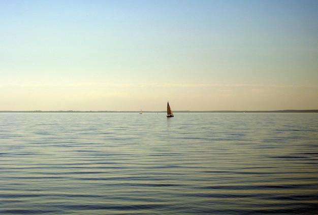Маленькая яхта плывет по реке на закате