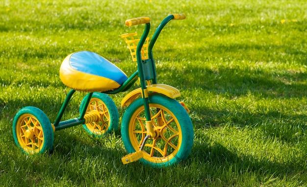 화창한 날 잔디 위에 서 있는 작은 노란색과 녹색 어린이 세발자전거. 공간을 복사합니다.