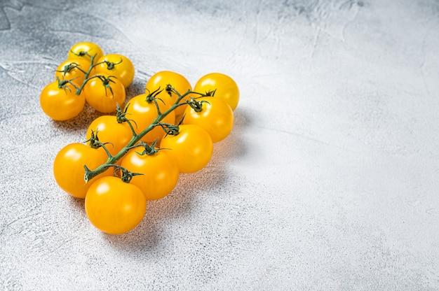 식탁에 작은 노란색 체리 토마토. 흰 바탕. 평면도. 공간을 복사합니다.
