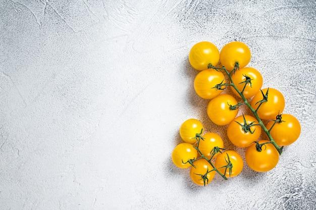 台所のテーブルの上の小さな黄色いチェリートマト。白いテーブル。上面図。