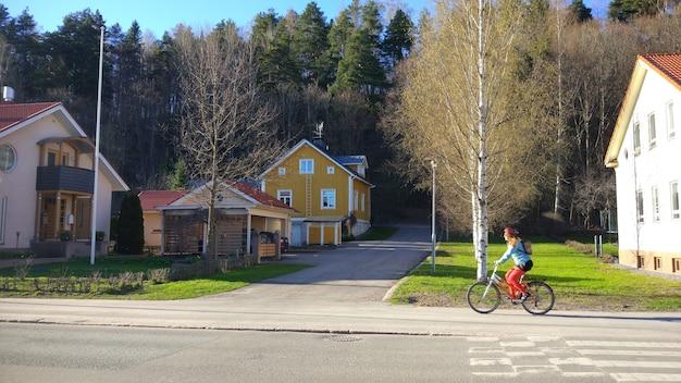 자전거 타는 사람이 있는 유럽 마을의 작은 노란색 시골집