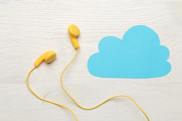 작은 노란색 헤드폰과 흰색 나무 배경에 파란색 종이 구름. 평면도