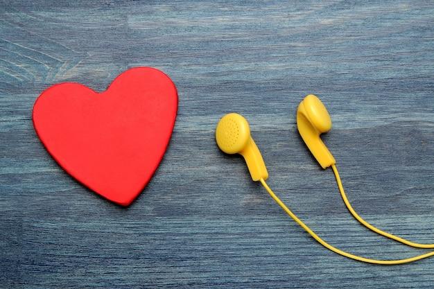 파란색 나무 배경에 작은 노란색 헤드폰과 빨간색 장식 심장. 평면도