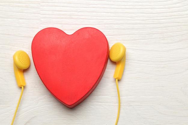 작은 노란색 헤드폰과 흰색 나무 바탕에 빨간색 장식 심장. 평면도