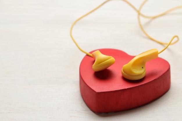작은 노란색 헤드폰과 흰색 나무 바탕에 빨간색 장식 심장.