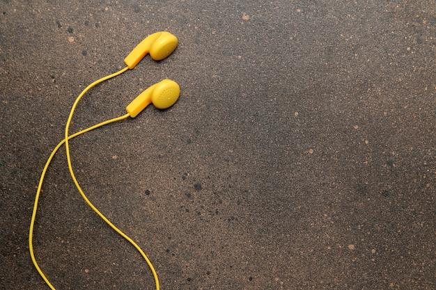 어두운 배경에 스마트폰용 작은 노란색 헤드폰. 평면도. 텍스트를 위한 공간