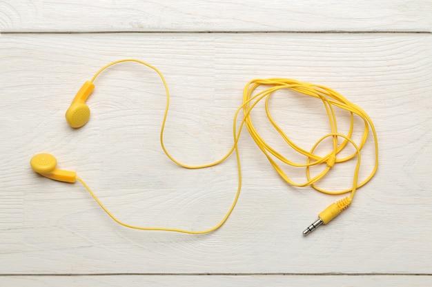흰색 나무 바탕에 스마트폰용 작은 노란색 헤드폰. 평면도