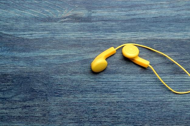 푸른 나무 배경에 스마트폰용 작은 노란색 헤드폰. 평면도. 자유 공간